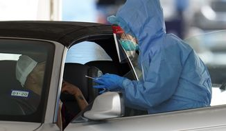 A patient is tested by a health care professional at a drive-thru testing site for COVID-19 at United Memorial Medical Center on Thursday, March 19, 2020, in Houston. For most people, the coronavirus causes only mild or moderate symptoms, such as fever and cough. For some, especially older adults and people with existing health problems, it can cause more severe illness, including pneumonia. (AP Photo/David J. Phillip)