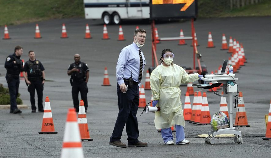Health care workers wait to swab for samples at a drive-through coronavirus collection site in Arlington, Va., Thursday, March 19, 2020. (AP Photo/J. Scott Applewhite) **FILE**