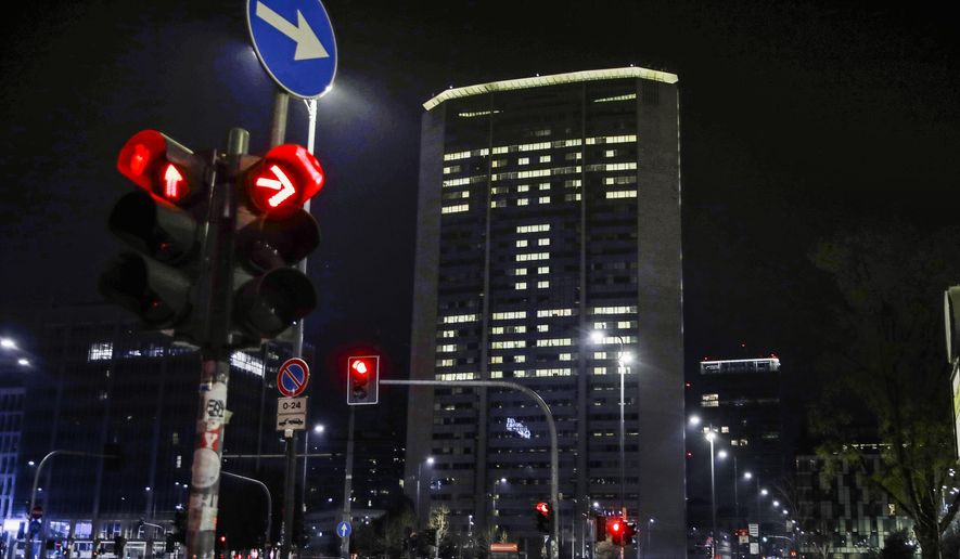 """Office lights of the Lombardy region headquarters building in Milan, northern Italy, compose the Italian words """"State a casa"""" (Stay home), Wednesday, March 18, 2020. (AP Photo/Luca Bruno)"""
