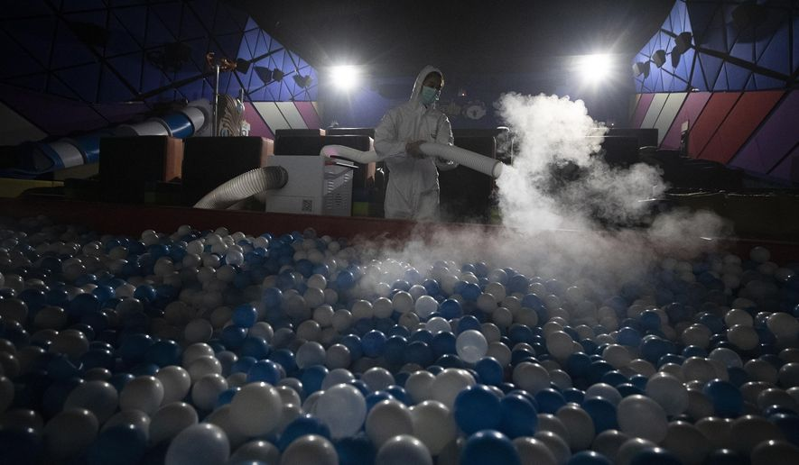 A worker sprays disinfectant as a precaution against the new coronavirus on ball pool for Kids Cinema at Quartier Cineart movie theater in Bangkok, Thailand, Thursday, March 19, 2020. Thailand's government has enacted stronger measures to combat the spread of the coronavirus, including postponing the country's biggest holiday, shutting down schools, movie theaters and closing bars. For most people, the new coronavirus causes only mild or moderate symptoms. For some it can cause more severe illness. (AP Photo/Sakchai Lalit)