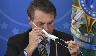Brazil's President Jair Bolsonaro puts on a mask during a press conference on the new coronavirus at the Planalto Presidential Palace in Brasilia, Brazil, Wednesday, March 18, 2019. For most people COVID-19 causes mild or moderate symptoms. For others, especially the elderly and people with existing health problems, it can cause many other serious illnesses, including pneumonia. (AP Photo/Andre Borges)