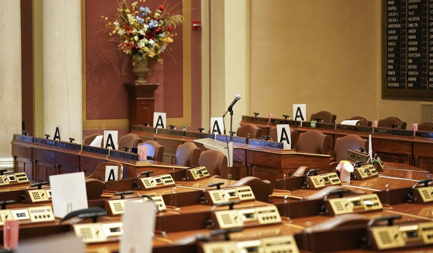"The House chamber at the state Capitol is empty Wednesday, March 18, 2020, in St. Paul, Minn., with some desks marked with an ""A"" - those desks may be occupied to maintain social distancing because of the coronavirus when lawmakers return. (Glen Stubbe/Star Tribune via AP)"