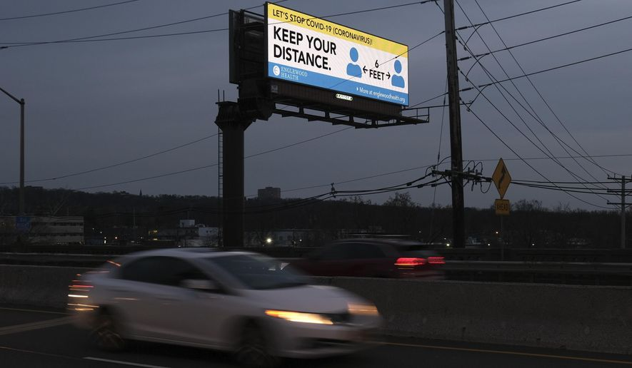 A billboard displays a message about the new coronavirus in Englewood, N.J., Wednesday, March 18, 2020. New Jersey expanded coronavirus mitigation efforts, ordering indoor malls and amusement centers closed, adding to the theaters, casinos, gyms and dining rooms it shuttered earlier this week. (AP Photo/Seth Wenig)