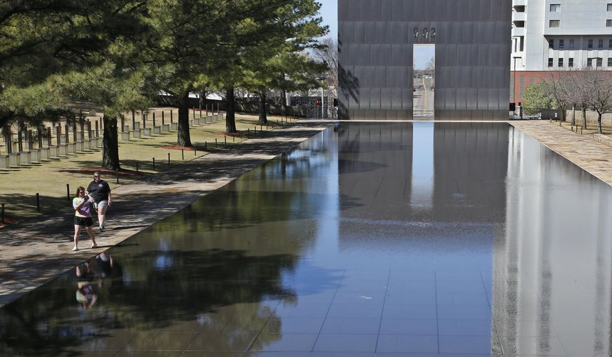 Visitors walk next to the reflecting pool at the Oklahoma City National Memorial and Museum in Oklahoma City, Wednesday, March 18, 2020. The Oklahoma City National Memorial and Museum has announced that it will offer a recorded, one-hour television program in place of a live ceremony to mark the 25th anniversary of the Oklahoma City bombing due to concerns about the spread of the coronavirus. (AP Photo/Sue Ogrocki)
