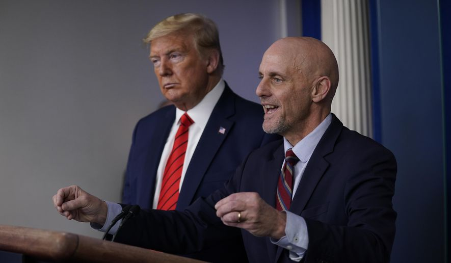 President Donald Trump, left, listens as Food and Drug Administration Commissioner Dr. Stephen Hahn speaks during a press briefing with the coronavirus task force, at the White House, Thursday, March 19, 2020, in Washington. (AP Photo/Evan Vucci)