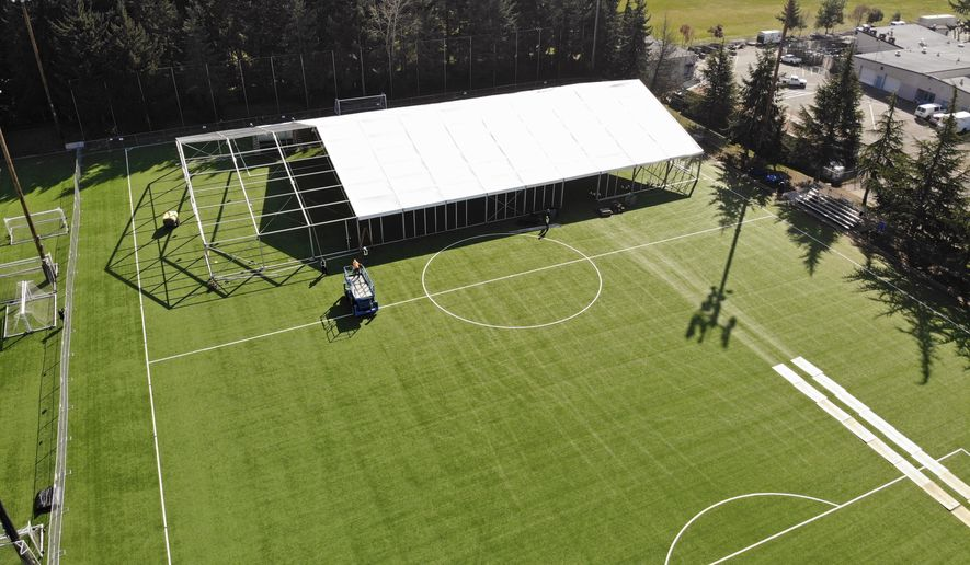 """In this aerial drone photo, workers erect a temporary field hospital for use by people unable to isolate and recover from COVID-19 in their own homes on a soccer field Thursday, March 19, 2020, in the Seattle suburb of Shoreline, Wash. The field hospital will provide up to 200 beds, according to a city website, and will house """"people exposed to, at risk of exposure, or becoming ill with the novel coronavirus."""" (AP Photo/Elaine Thompson)"""