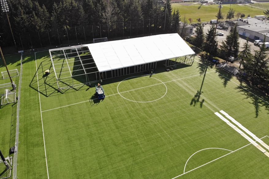 "In this aerial drone photo, workers erect a temporary field hospital for use by people unable to isolate and recover from COVID-19 in their own homes on a soccer field Thursday, March 19, 2020, in the Seattle suburb of Shoreline, Wash. The field hospital will provide up to 200 beds, according to a city website, and will house ""people exposed to, at risk of exposure, or becoming ill with the novel coronavirus."" (AP Photo/Elaine Thompson)"