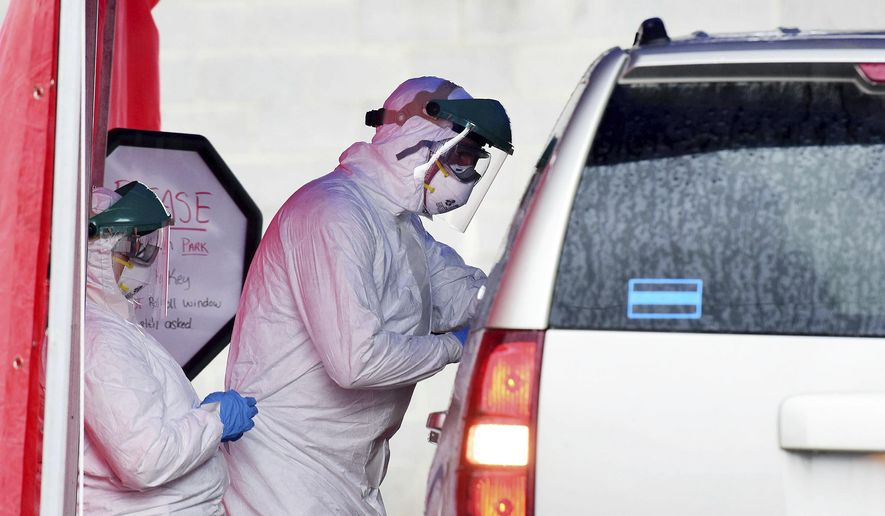 Clinical care providers take swabs for coronavirus on a patient during drive-thru testing by the Fayette County Health Department in Oak Hill, W.V. on Thursday, March 19, 2020. (Chris Jackson/The Register-Herald via AP)