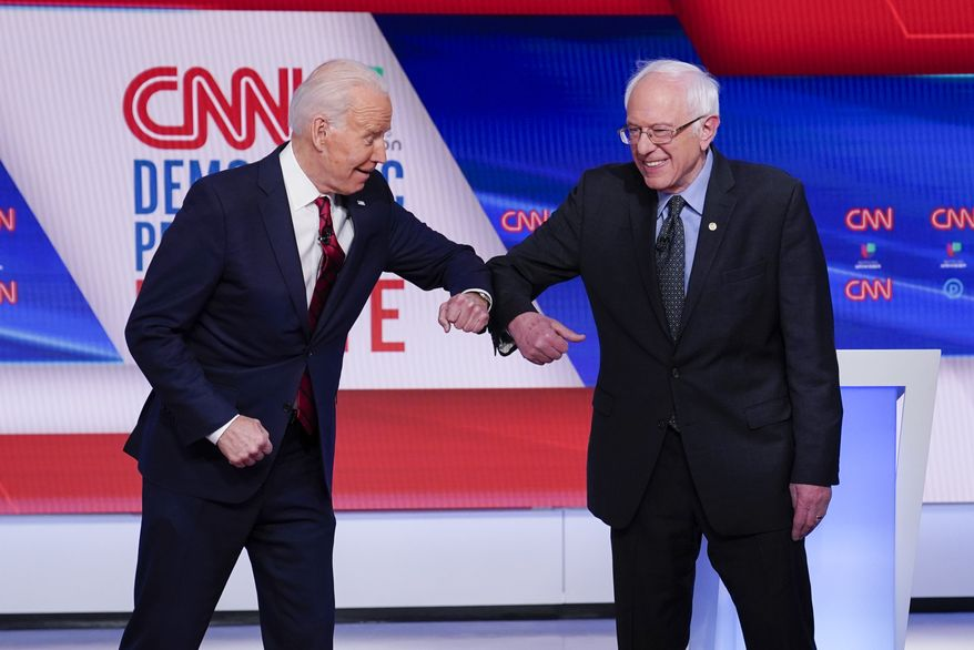 Former Vice President Joe Biden, left, and Sen. Bernie Sanders, I-Vt., right, greet one another before they participate in a Democratic presidential primary debate at CNN Studios in Washington, Sunday, March 15, 2020. (AP Photo/Evan Vucci)