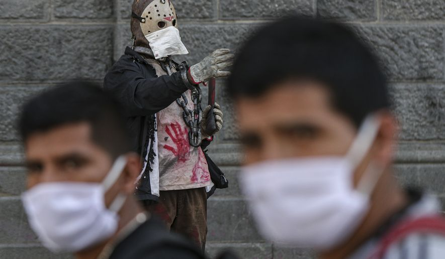 """Street performer Leo Aguilera is dressed as Jason, a character from  the """"Friday the 13th"""" film, uses a face mask as a precaution against the spread of the new coronavirus, in downtown Santiago, Chile, Friday, March 20, 2020. (AP Photo/Esteban Felix)"""