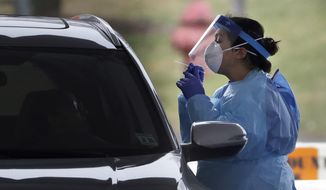 A medical staff member in protective gear administers a test for COVID-19 at a drive-through testing center in Paramus, N.J., Friday, March 20, 2020. (AP Photo/Seth Wenig)