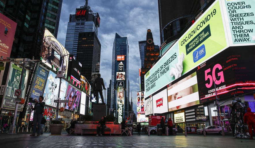 """A screen displaying messages concerning COVID-19 is seen in a sparsely populated Times Square, Friday, March 20, 2020, in New York. New York Gov. Andrew Cuomo is ordering all workers in non-essential businesses to stay home and banning gatherings statewide. """"Only essential businesses can have workers commuting to the job or on the job,"""" Cuomo said of an executive order he will sign Friday. Nonessential gatherings of individuals of any size or for any reason are canceled or postponed. (AP Photo/John Minchillo)"""