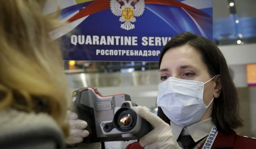 An employee of the Russian Federal Service for Surveillance on Consumer Rights Protection and Human Wellbeing (Rospotrebnadzor) checks the body temperature of a woman arriving at Pulkovo airport in St. Petersburg, Russia, Friday, March 20, 2020. (AP Photo/Dmitri Lovetsky)