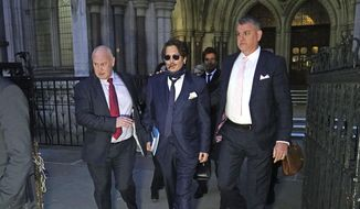 Actor Johnny Depp, center, leaves the High Court in London, after attending a preliminary hearing in his libel case against the publishers of The Sun and its executive editor, Dan Wootton, over a 2018 article alleging he had been abusive to his ex-wife Amber Heard, Wednesday, Feb. 26, 2020. (Aaron Chown/PA via AP) ** FILE **