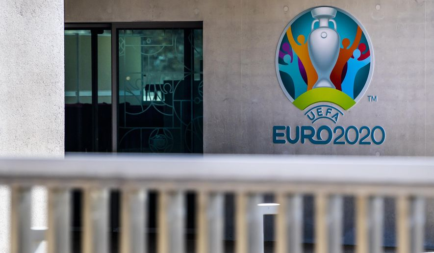 The Euro 2020 logo displayed next to the entrance of the UEFA Headquarters, in Nyon, Switzerland, Tuesday, March 17, 2020. The UEFA meet on 17 March 2020 to discuss the effects of the coronavirus pandemic on the UEFA EURO 2020 and the European Cup competitions. For most people, the new coronavirus causes only mild or moderate symptoms, such as fever and cough. For some, especially older adults and people with existing health problems, it can cause more severe illness, including pneumonia. (Jean-Christophe Bott/Keystone via AP)