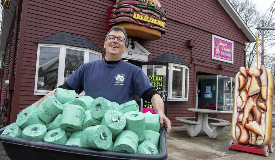 Vinny Iannuzzi, the owner of Vinny's Deli on Center Street in Wallingford, holds toilet paper he has at his deli on Thursday, March 19. 2020. He is giving away a roll of toilet paper with every sandwich when you show them the coupon from their social media pages. (Aaron Flaum/Record-Journal via AP)