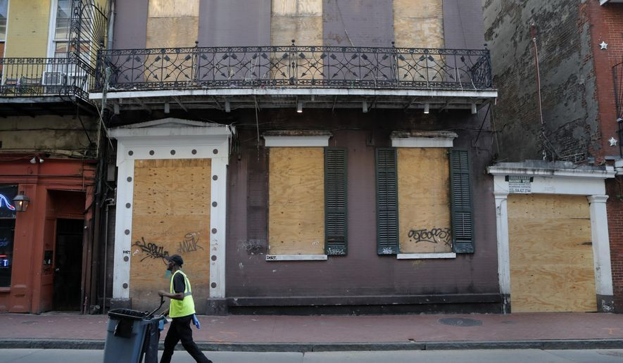 A boarded business is seen boarded up on Bourbon Street, usually bustling with tourists and revelers, in the French Quarter of New Orleans, Thursday, March 19, 2020. Louisiana Governor John Bel Edwards and New Orleans Mayor Latoya Cantrell have ordered all restaurants and bars to close except for takeout, and asked residents to remain home and maintain social distancing from others when outside, due to the COVID-19 virus pandemic. (AP Photo/Gerald Herbert)