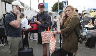 Tourists from the United States wait outside the closed Jorge Chavez International Airport for a member of the U.S. Embassy to escort them to a flight that will fly them back to the U.S., in Callao Peru, Friday, March 20, 2020, on the fifth day of a state of emergency decreed by the government to prevent the spread of the new coronavirus.  (AP Photo/Martin Mejia)