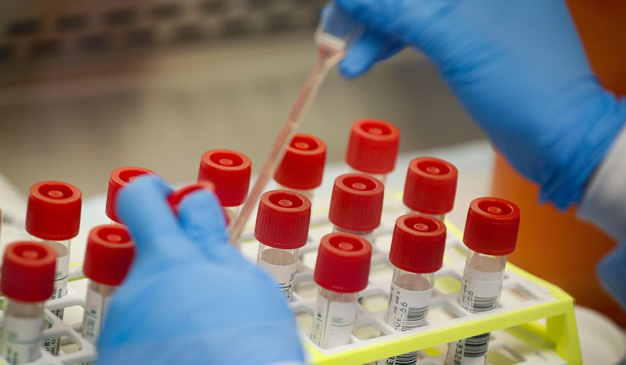 In this Wednesday, March 11, 2020, file photo, a technician prepares COVID-19 patient samples for testing at a laboratory in New York's Long Island. (AP Photo/John Minchillo) ** FILE **