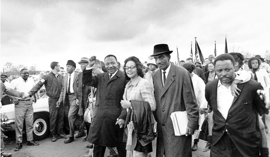 FILE - In this March 25, 1965, file photo, Dr. Martin Luther King Jr., and his wife, Coretta Scott King, lead off the final lap to the state capitol at Montgomery, Ala., as thousands of civil rights marchers joined in the walk to demand voter registration rights for blacks. A new project launched in March 2020 by the Hutchins Center for African and African American Research at Harvard University and a coalition of foundations seeks to bring online, interactive lessons about Selma and voting rights to students who are home from school due to the novel coronavirus. (AP Photo, File)