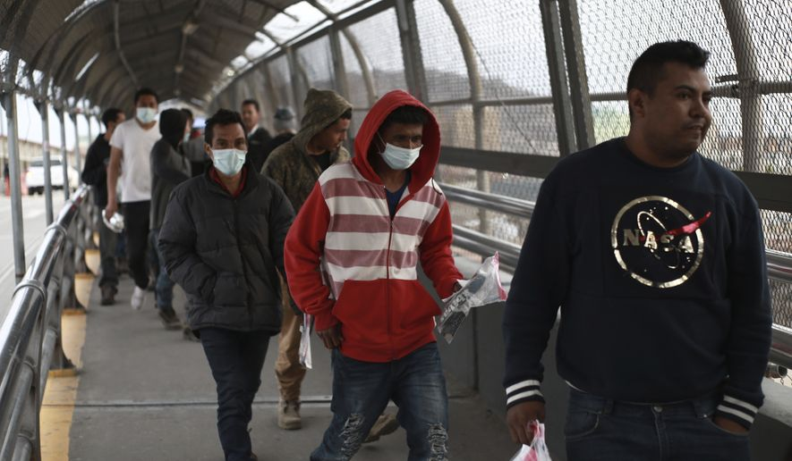 Central American migrants seeking asylum, some wearing protective face masks, return to Mexico via the international bridge at the U.S-Mexico border that joins Ciudad Juarez and El Paso, Saturday, March 21, 2020. Mexico and the U.S. are restricting travel over their busy shared border as they try to control the spread of the coronavirus pandemic. (AP Photo/Christian Chavez)