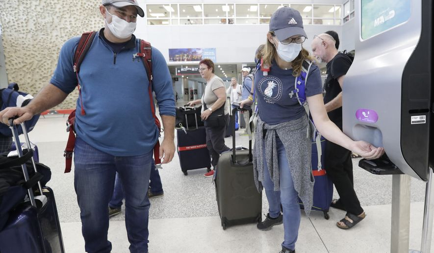 Linda Scruggs, right, applies hand sanitizer as Mike Rustici, left, watches after they arrived on a flight from Lima, Peru, Saturday, March 21, 2020, at Miami International Airport in Miami. The pair's plight illustrates the desperation people stuck abroad experienced as the COVID-19 pandemic spread. Peru confirmed its first case of the virus on March 6. By the time Scruggs and Rustici arrived a week later, it was spreading. (AP Photo/Wilfredo Lee)