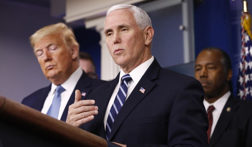 President Donald Trump listens as Vice President Mike Pence speaks during a coronavirus task force briefing at the White House, Saturday, March 21, 2020, in Washington. Housing and Urban Development Secretary Ben Carson is at right. (AP Photo/Patrick Semansky)