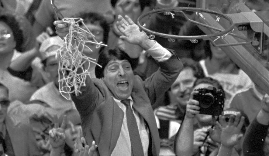 In this April 4, 1983 file photo, North Carolina State coach Jim Valvano holds the net aloft after his team defeated Houston 54-52 for the national championship at the Final Four NCAA college basketball tournament in Albuquerque, N.M. (AP Photo/Leonard Ignelzi, File) **FILE**