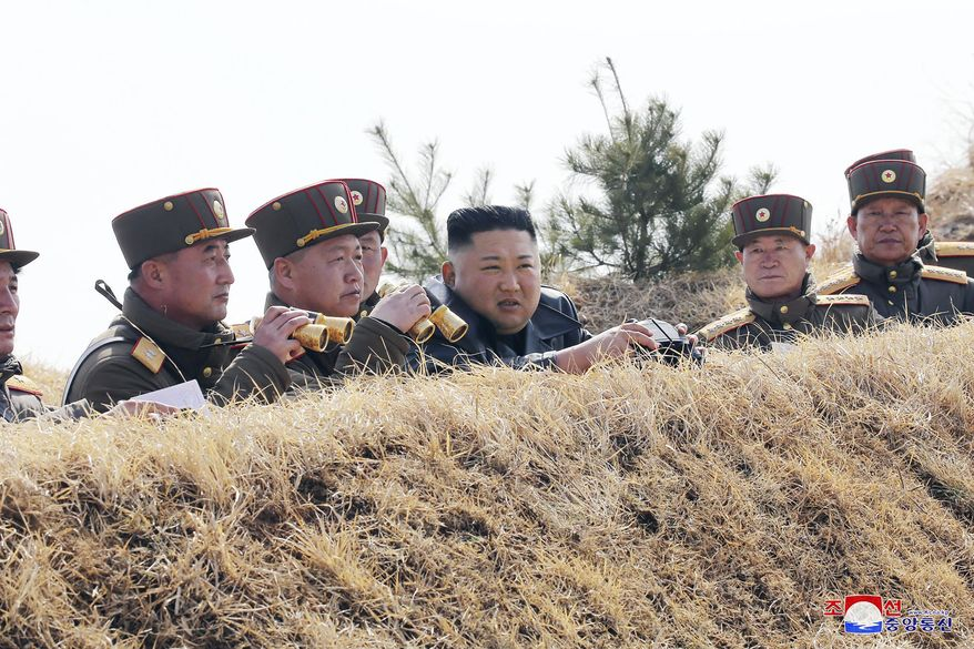 """In this Friday, March 20, 2020, photo provided by the North Korean government, North Korean leader Kim Jong Un supervises an artillery firing competition between army units in the country's west in North Korea. Independent journalists were not given access to cover the event depicted in this image distributed by the North Korean government. The content of this image is as provided and cannot be independently verified. Korean language watermark on image as provided by source reads: """"KCNA"""" which is the abbreviation for Korean Central News Agency. (Korean Central News Agency/Korea News Service via AP)"""