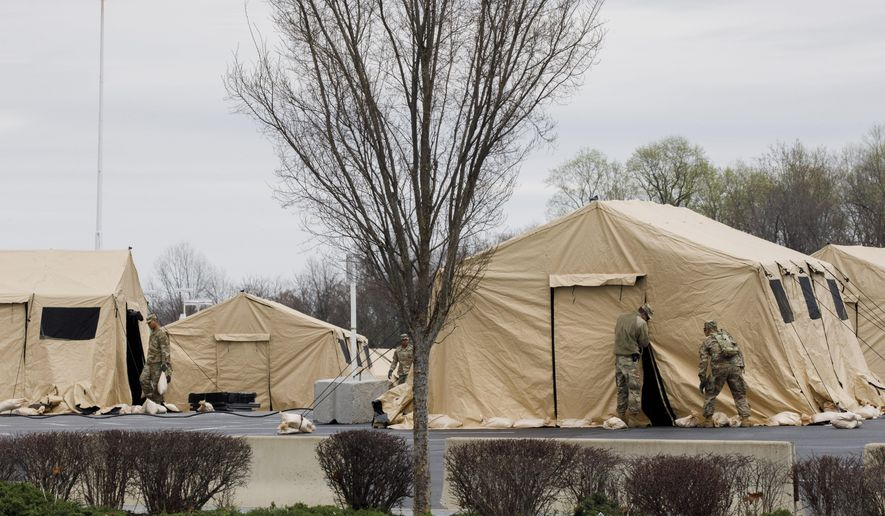 The National Guard sets up tents to be used for coronavirus testing, Saturday, March 21, 2020, in a parking lot for FedEx Field in Landover, Md., outside of Washington. (AP Photo/Jacquelyn Martin)