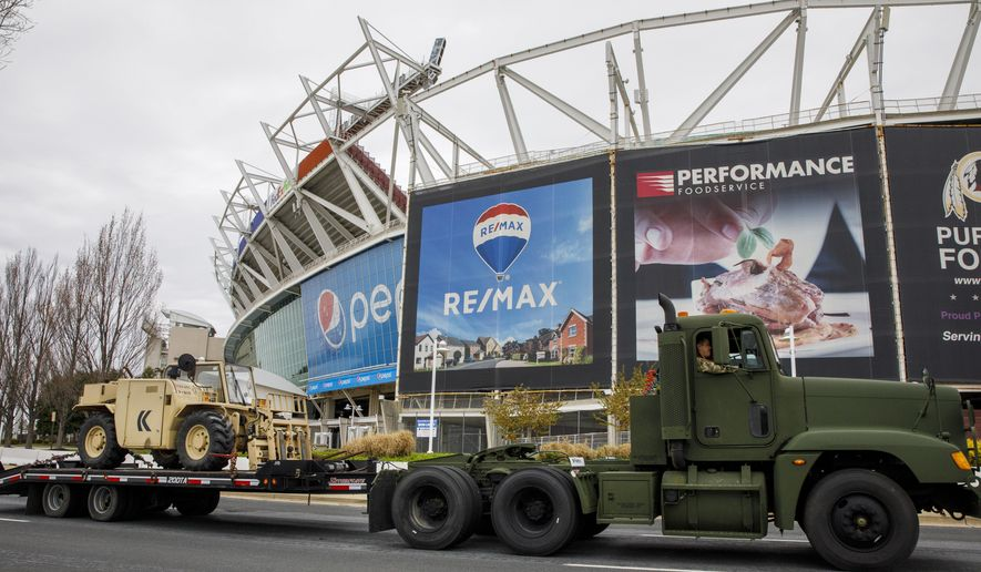 Equipment is driven by FedEx Field as the National Guard sets up tents to be used for coronavirus testing, Saturday, March 21, 2020, in a parking lot at the NFL football stadium in Landover, Md., outside of Washington. (AP Photo/Jacquelyn Martin) ** FILE **