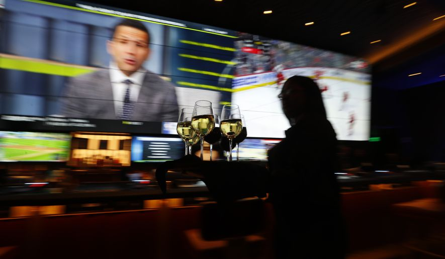 A waitress carries glasses of wine at a MGM Grand Detroit casino bar in Detroit, Wednesday, March 11, 2020. (AP Photo/Paul Sancya)