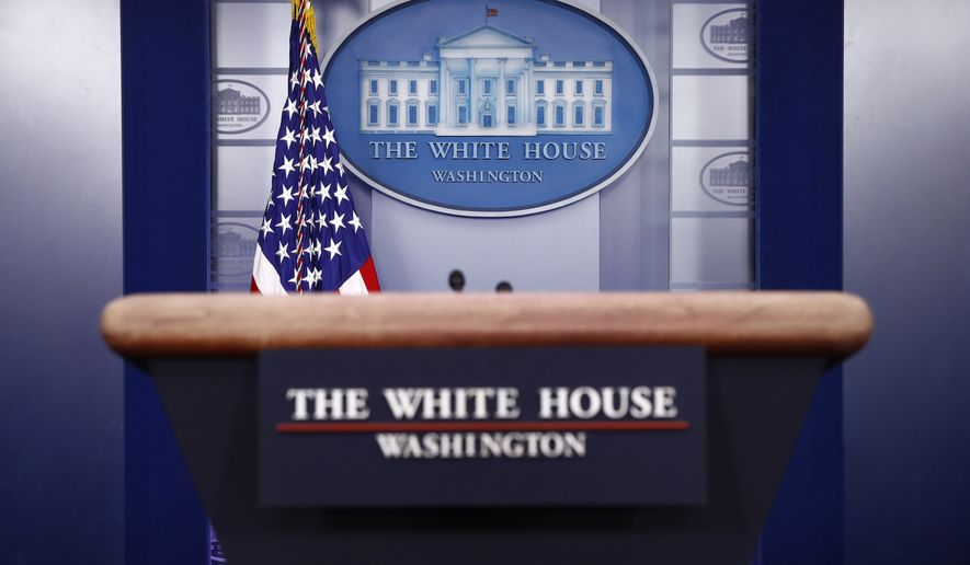A plaque depicting the White House is posted behind a podium in the James Brady Press Briefing Room of the White House, Sunday, March 22, 2020, in Washington. (AP Photo/Patrick Semansky)