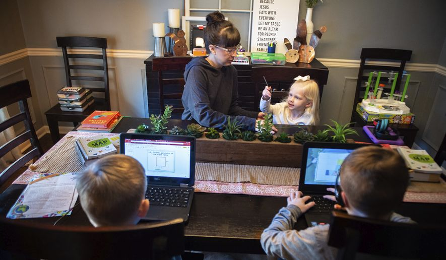 Emily Williams, third-grade teacher of Austinville Elementary, left, helps her daughter Lily, 3, as her two sons Braden, 10, bottom left, and Landen, 8, complete school assigned virtual assignments on Friday, March 20, 2020, at their home in Decatur, Ala. (Dan Busey/The Decatur Daily via AP)  **FILE**