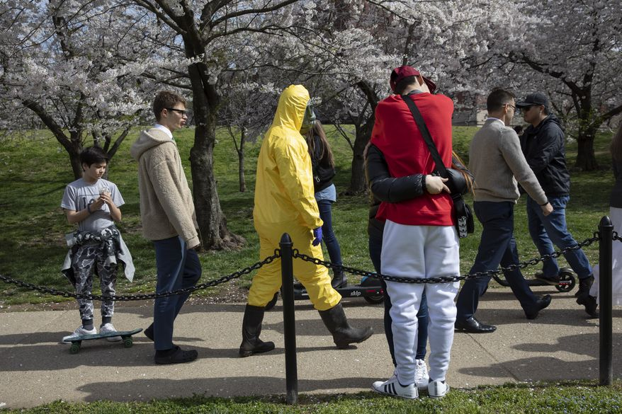 """A 17-year-old who asked not to be named wears a yellow hazmat suit, gas mask, boots, and gloves as he walks past a couple in an embrace, as he and his family from Gaithersburg, Md. walk under cherry blossom trees in full bloom on their way to the tidal basin, Sunday, March 22, 2020, in Washington. """"I'm not worried for me since I'm young,"""" says the 17-year-old, """"I'm wearing this in case I come into contact with anyone who is older so that I won't be a threat to them."""" He plans to wear his protective outfit for coronavirus each time he leaves the house. Sections of the National Mall and tidal basin areas have been closed to vehicular traffic to encourage people to practice social distancing and not visit Washington's iconic cherry blossoms this year due to coronavirus concerns. The trees are in full bloom this week and would traditionally draw a large crowd. (AP Photo/Jacquelyn Martin)"""