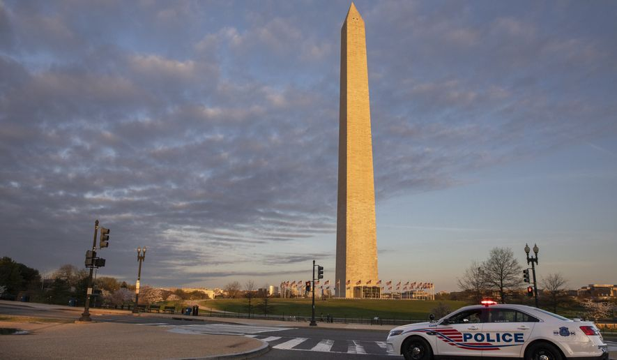 A District of Columbia Police Car blocks the road near the Washington Monument in an effort to discourage crowds from visiting the cherry blossom trees in full bloom, Sunday, March 22, 2020, in Washington. (AP Photo/Jacquelyn Martin)