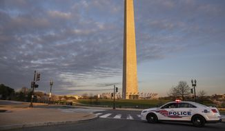 A Metropolitan Police Department car blocks the road near the Washington Monument in an effort to discourage crowds from visiting the cherry blossom trees in full bloom, Sunday, March 22, 2020, in Washington, D.C. (AP Photo/Jacquelyn Martin) ** FILE **