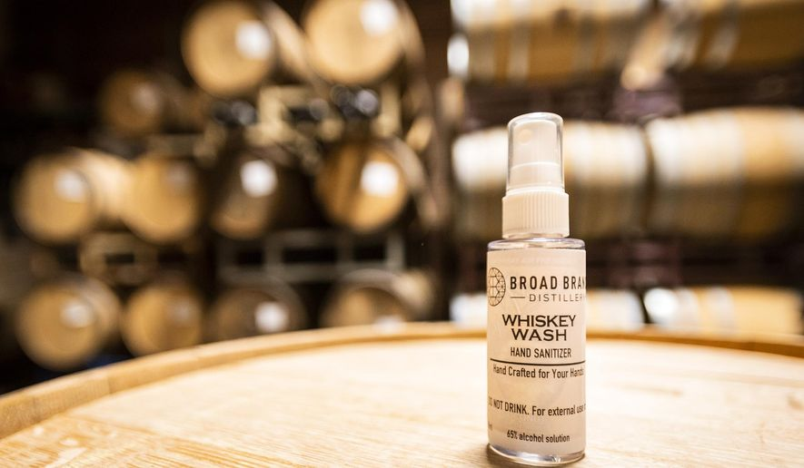 A bottle of Broad Branch Distillery's Whiskey Wash Hand Sanitizer sits on a barrel on Wednesday, March 18, 2020 in Winston-Salem, N.C. The distillery is creating hand sanitizer, which is available for free to the public, in reaction to the outbreak of the COVID-19 virus. (Andrew Dye/The Winston-Salem Journal via AP)