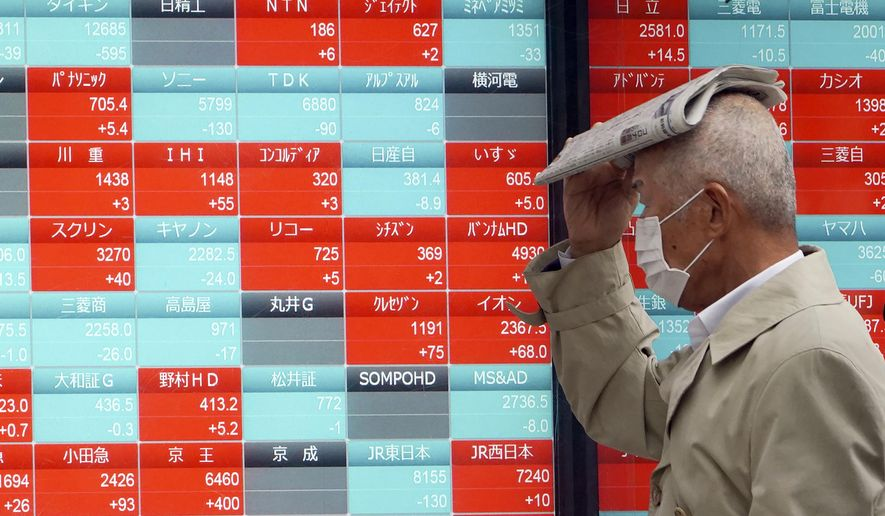 A man with a protective mask in the rain looks at an electronic stock board showing Japan's Nikkei 225 index at a securities firm in Tokyo Monday, March 23, 2020. Shares dropped in Hong Kong and South Korea early Monday. However, Japan's Nikkei 225 index held steady, gaining 0.8% on news the International Olympic Committee plans to discuss potentially changing the timing of the Tokyo Games, due to begin in July. (AP Photo/Eugene Hoshiko)