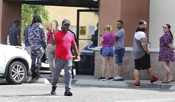 A gun owner leaves the Shoot Straight gun store in Casselberry, Fla., Sunday, March 22, 2020. Gun sales have increased nationwide in response to the coronavirus pandemic. (Joe Burbank/Orlando Sentinel via AP)