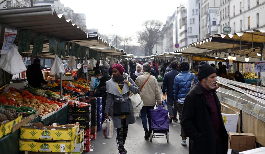 People walk in the open air market of Belleville, in Paris, Friday, March 20, 2020. French President Emmanuel Macron said that for 15 days starting at noon on Tuesday, people will be allowed to leave the place they live only for necessary activities such as shopping for food, going to work or taking a walk. For most people, the new coronavirus causes only mild or moderate symptoms. For some it can cause more severe illness, especially in older adults and people with existing health problems. (AP Photo/Thibault Camus)