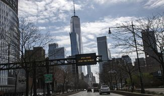 An electronic sign board urging citizens to stay home and stop the spread of the coronavirus is seen displayed above a road in the foreground of One World Trade Center in New York, on Sunday, March 22, 2020. New York City's mayor prepared Sunday to order his city behind closed doors in an attempt to slow a pandemic that has swept across the globe and threatened to make the city of 8.5 million one of the world's biggest coronavirus hot spots. (AP Photo/Wong Maye-E)