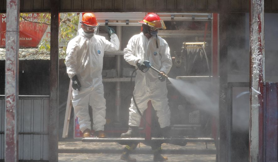 Sri Lankan fire brigade personnel spray disinfectants at a bus terminal in Colombo, Sri Lanka, Sunday, March 22, 2020. For most people, the new coronavirus causes only mild or moderate symptoms. For some it can cause more severe illness. (AP Photo/Eranga Jayawardena)