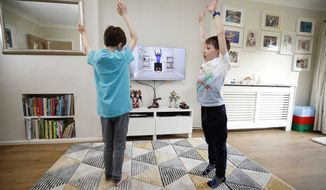 Ben and Isaac Rickett follow P.E with Joe, a fitness workout by fitness coach Joe Wicks, aimed at children that are being home schooled due to the outbreak of the coronavirus, in England, Monday March 23, 2020. For some people the coronavirus causes mild or moderate symptoms, but for others it causes severe illness. (Martin Rickett/PA via AP)