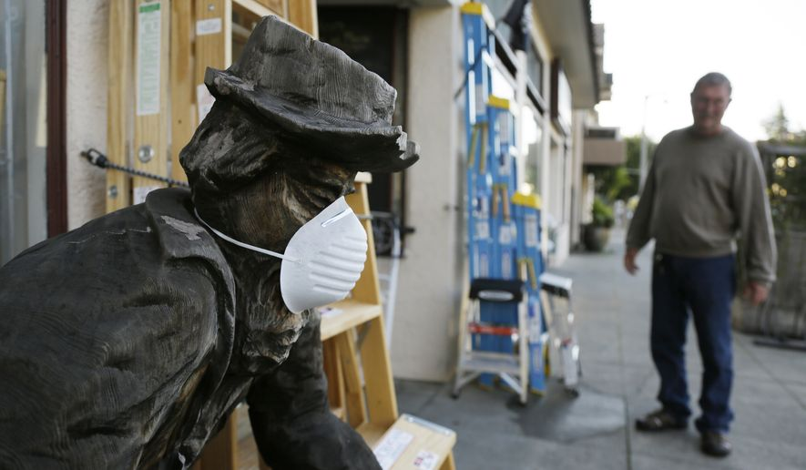 A wooden carving of a man panning for gold wears a protective mask outside the Waterstreet Hardware store Monday, March 23, 2020, in Sausalito, Calif. The old fashioned neighborhood hardware store is open, but operating under reduced shelter in place hours because of the coronavirus threat. (AP Photo/Eric Risberg)