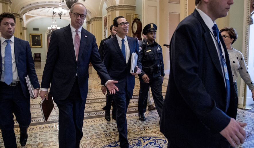 Treasury Secretary Steven Mnuchin, center, and White House Legislative Affairs Director Eric Ueland, second from left, walk to a meeting with Senate Minority Leader Sen. Chuck Schumer of N.Y. in his office on Capitol Hill, Monday, March 23, 2020, in Washington. The Senate is working to pass a coronavirus relief bill. (AP Photo/Andrew Harnik)