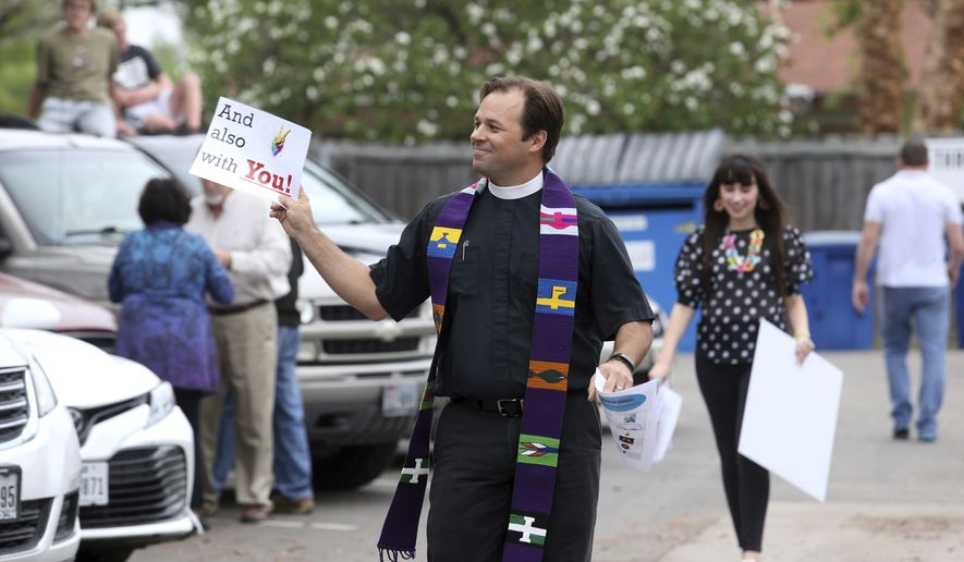 The Rev. Rod Clark, of St. John's Episcopal Church, holds Mass in the parking lot of the church that remains closed because of restrictions set in place due to concerns over the coronavirus on Sunday, March 22, 2020, in McAllen, Texas. (Delcia Lopez/The Monitor via AP)