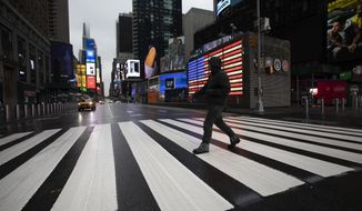 A man crosses the street in a nearly empty Times Square, which is usually very crowded on a weekday morning, Monday, March 23, 2020 in New York. Gov. Andrew Cuomo has ordered most New Yorkers to stay home from work to slow the coronavirus pandemic. (AP Photo/Mark Lennihan)  **FILE**