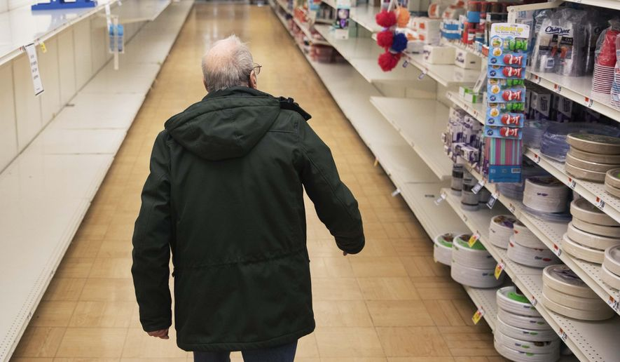 In this March 19, 2020, file photo, a shopper looks for toilet paper at a Stop & Shop supermarket during hours open daily only for seniors in North Providence, R.I. Federal law enforcement is warning that scam artists are preying on older people's fears by peddling fake tests for the coronavirus to Medicare recipients. (AP Photo/David Goldman)