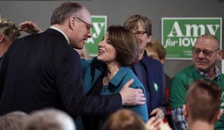 In this Feb. 1, 2020, file photo, Democratic presidential candidate Sen. Amy Klobuchar, D-Minn., center, gets a kiss from husband John Bessler, upon arriving at a rally in Sioux City, Iowa. Sen. Klobuchar announced Monday, March 23, that her husband has tested positive for the coronavirus. (AP Photo/Gene J. Puskar File)